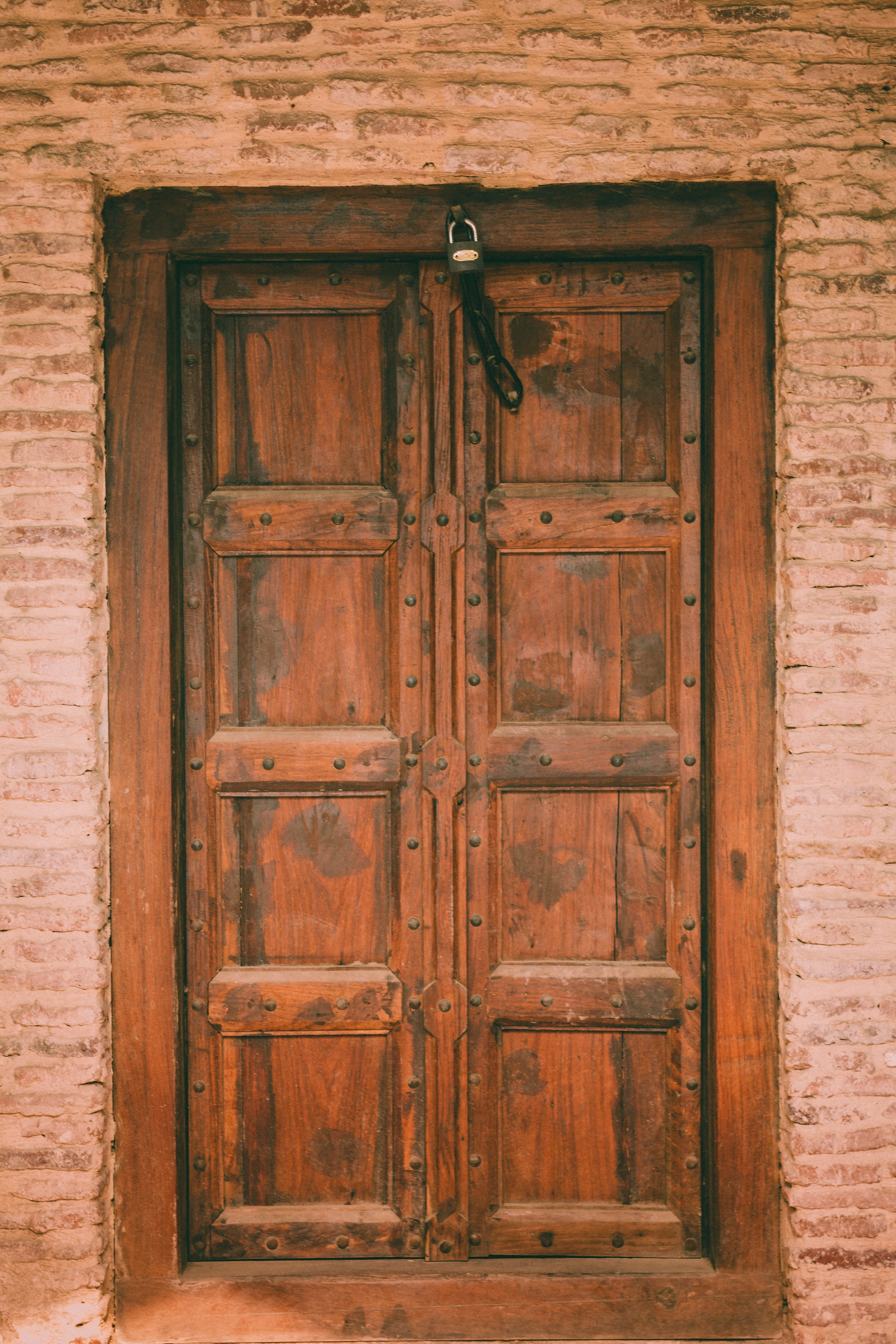 brown wooden door with padlock