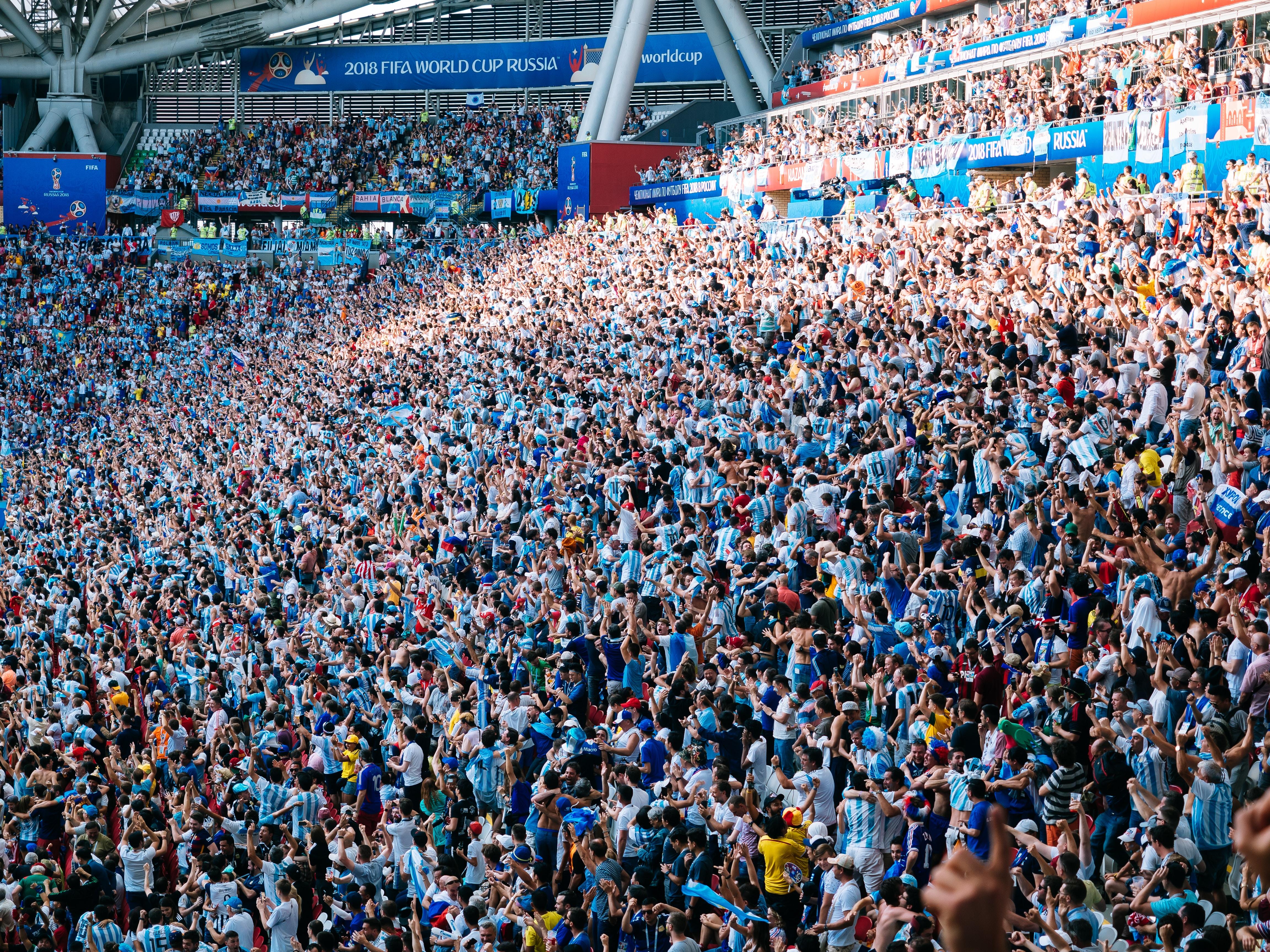 people cheering inside stadiums bleachers at daytime