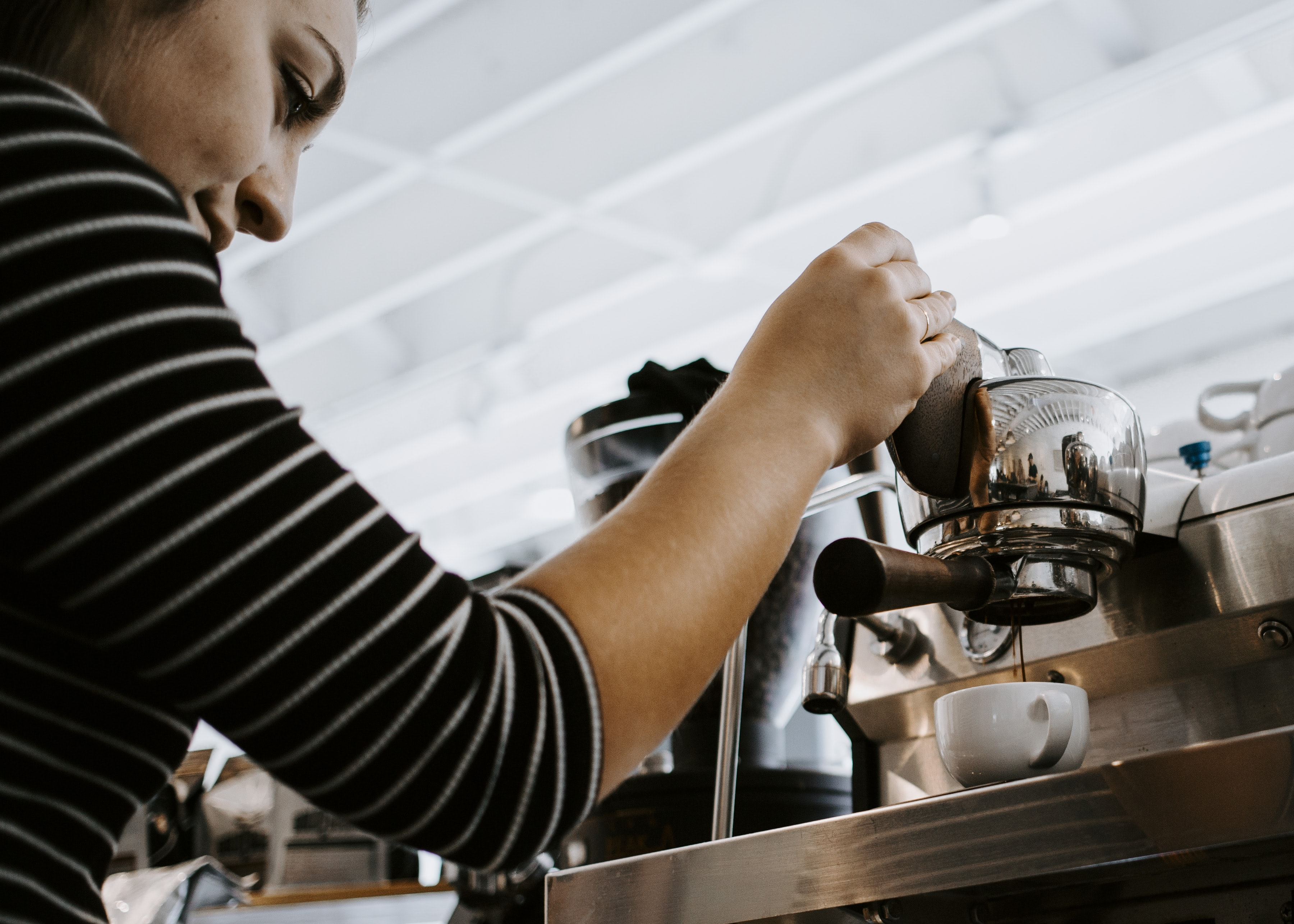 woman holding espresso machine pouring on teacup