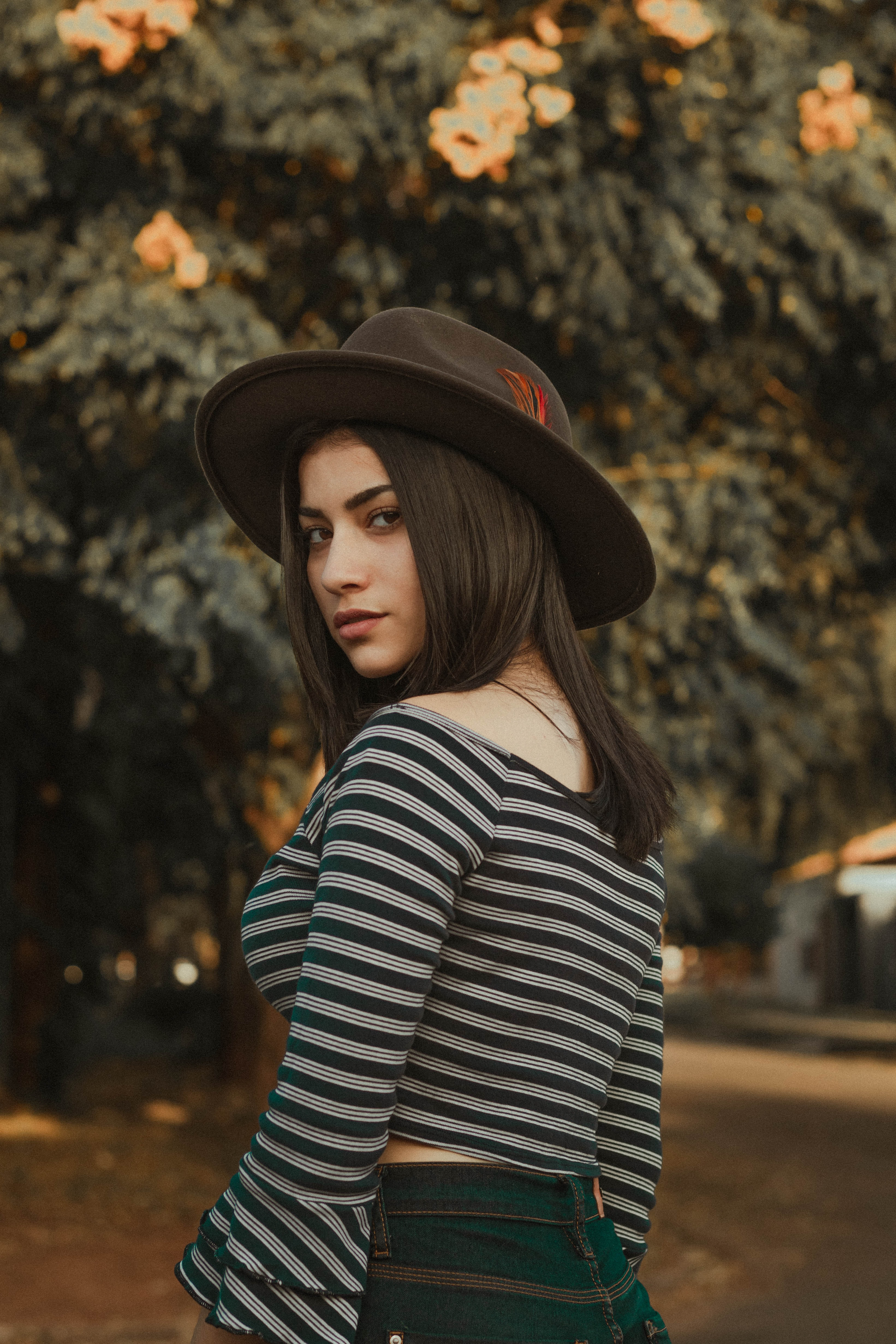 woman wearing gray and black striped shirt and black hat near green tree