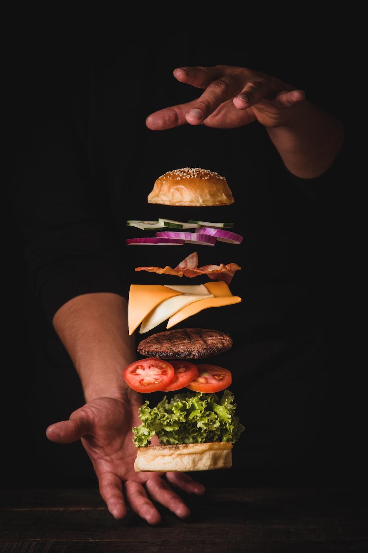 timelapse photo of man holding burger