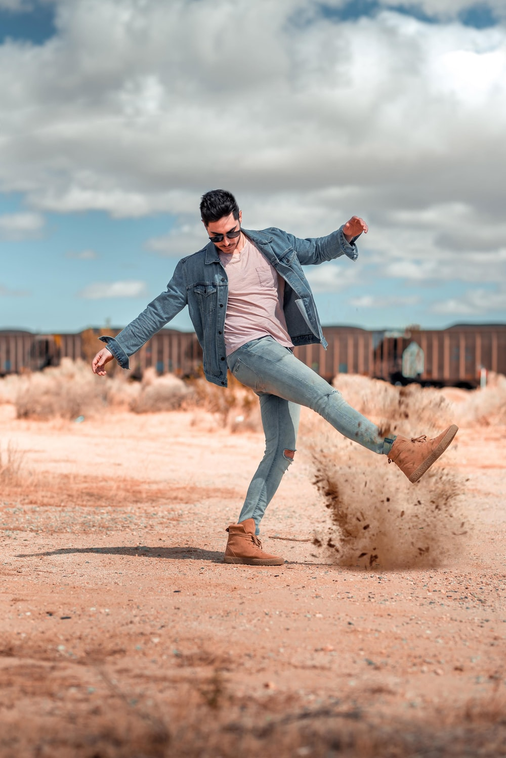man kicking brown ground under white clouds at daytime