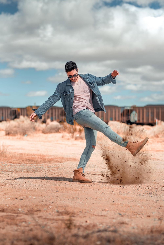 man kicking brown ground under white clouds at daytime