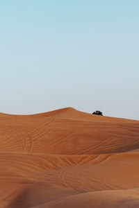 vehicle on desert under calm blue sky