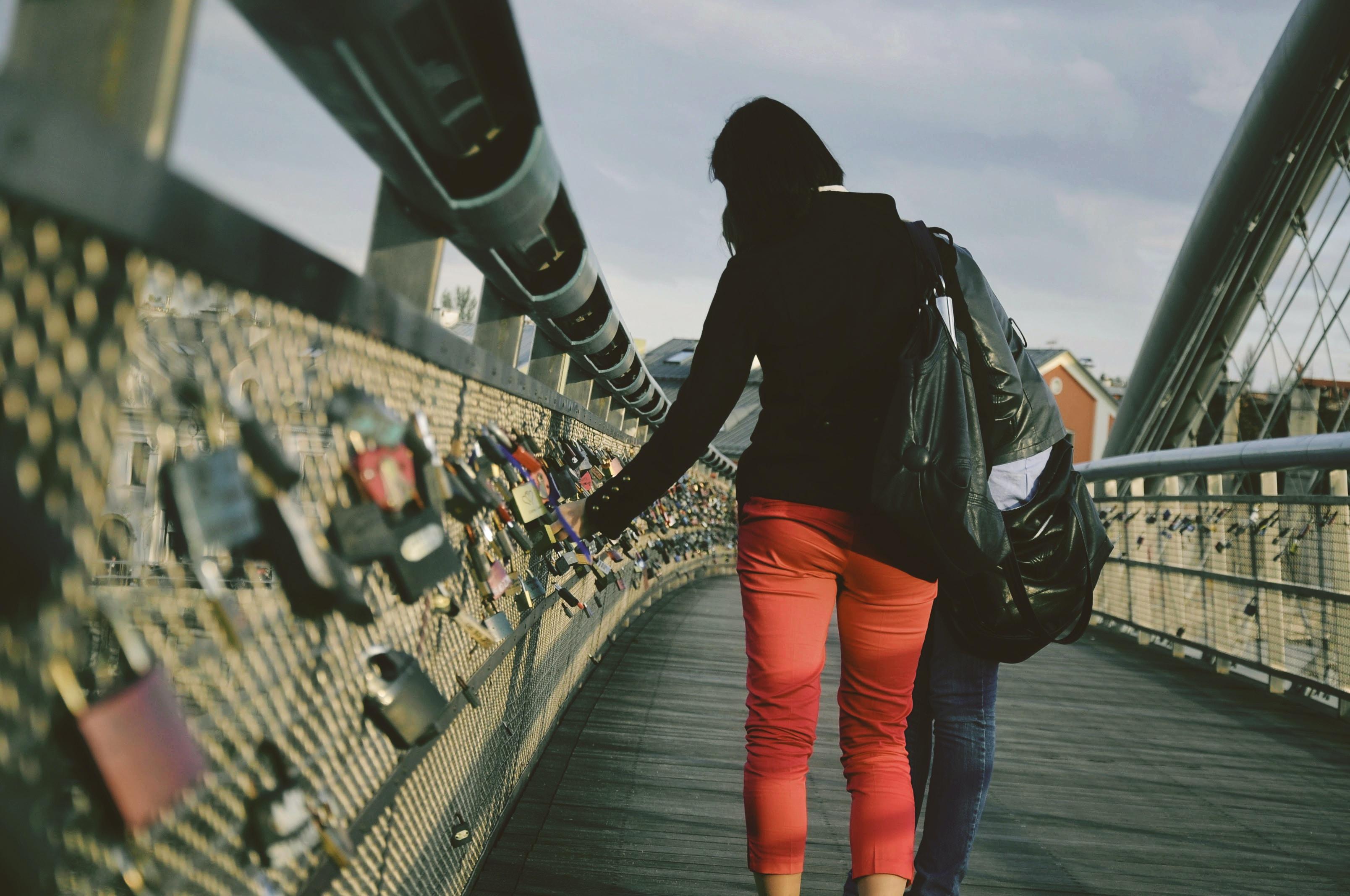 woman standing on bridge with locks