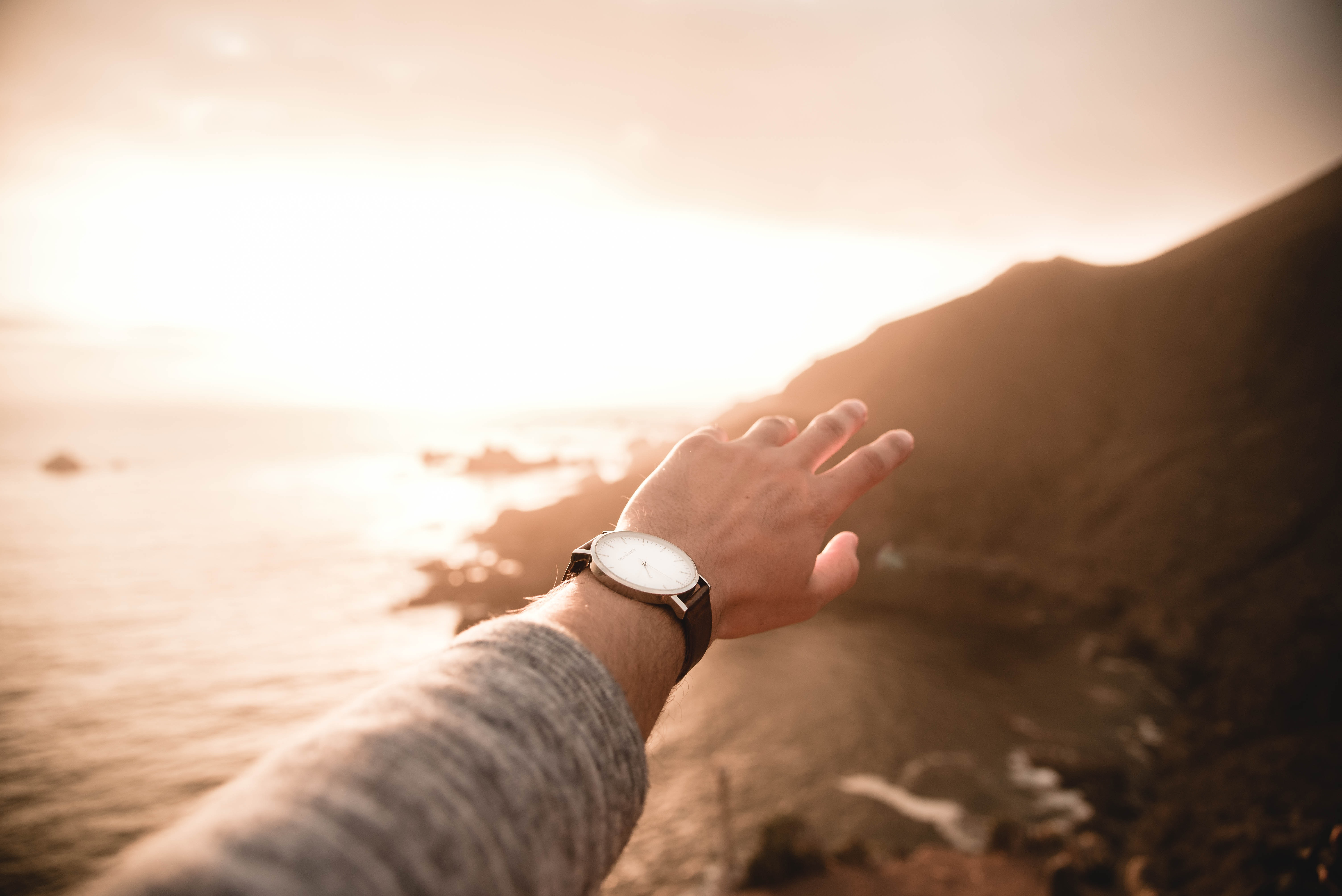 left person's arm wearing watch pointing body of water