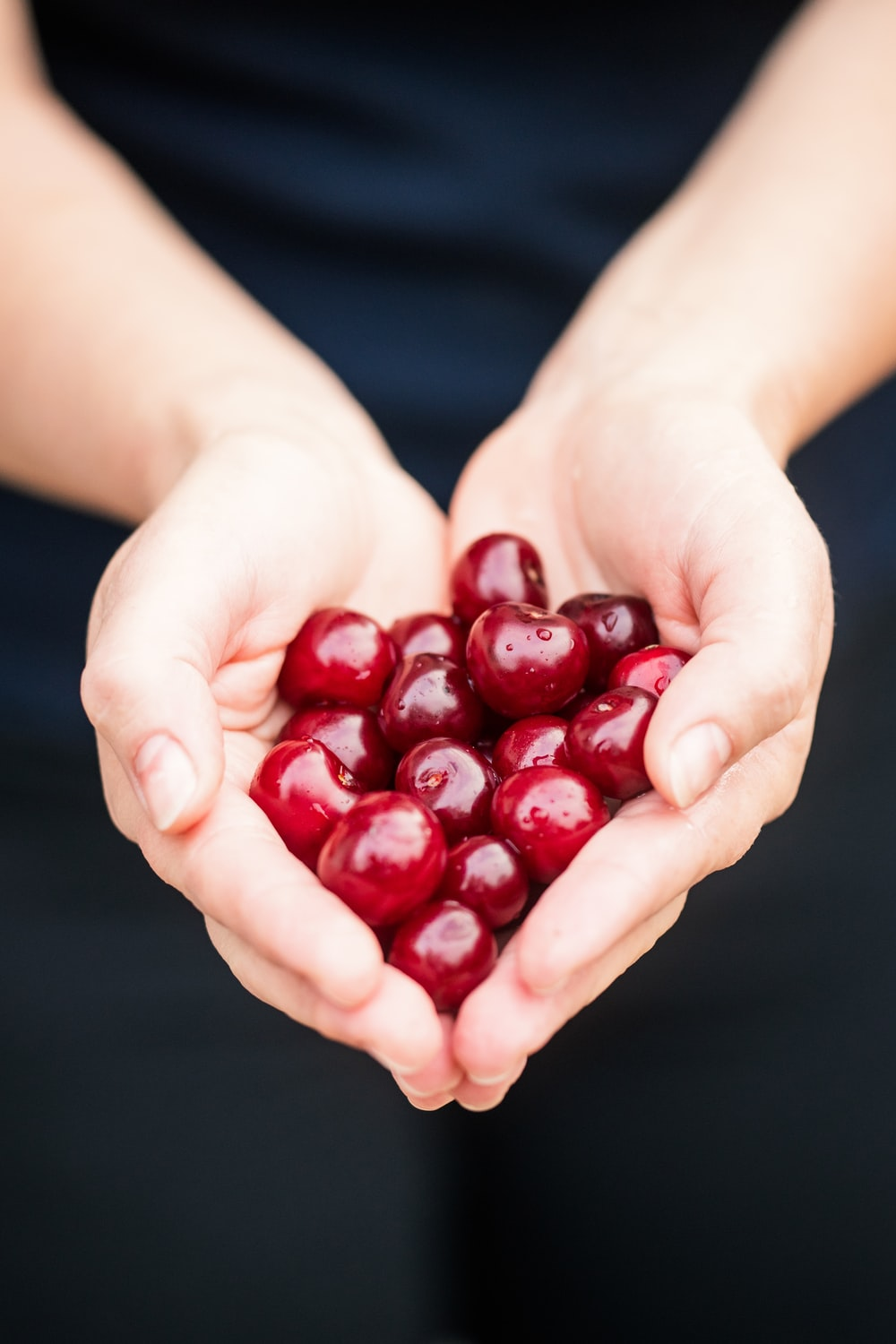 person holding red cherries