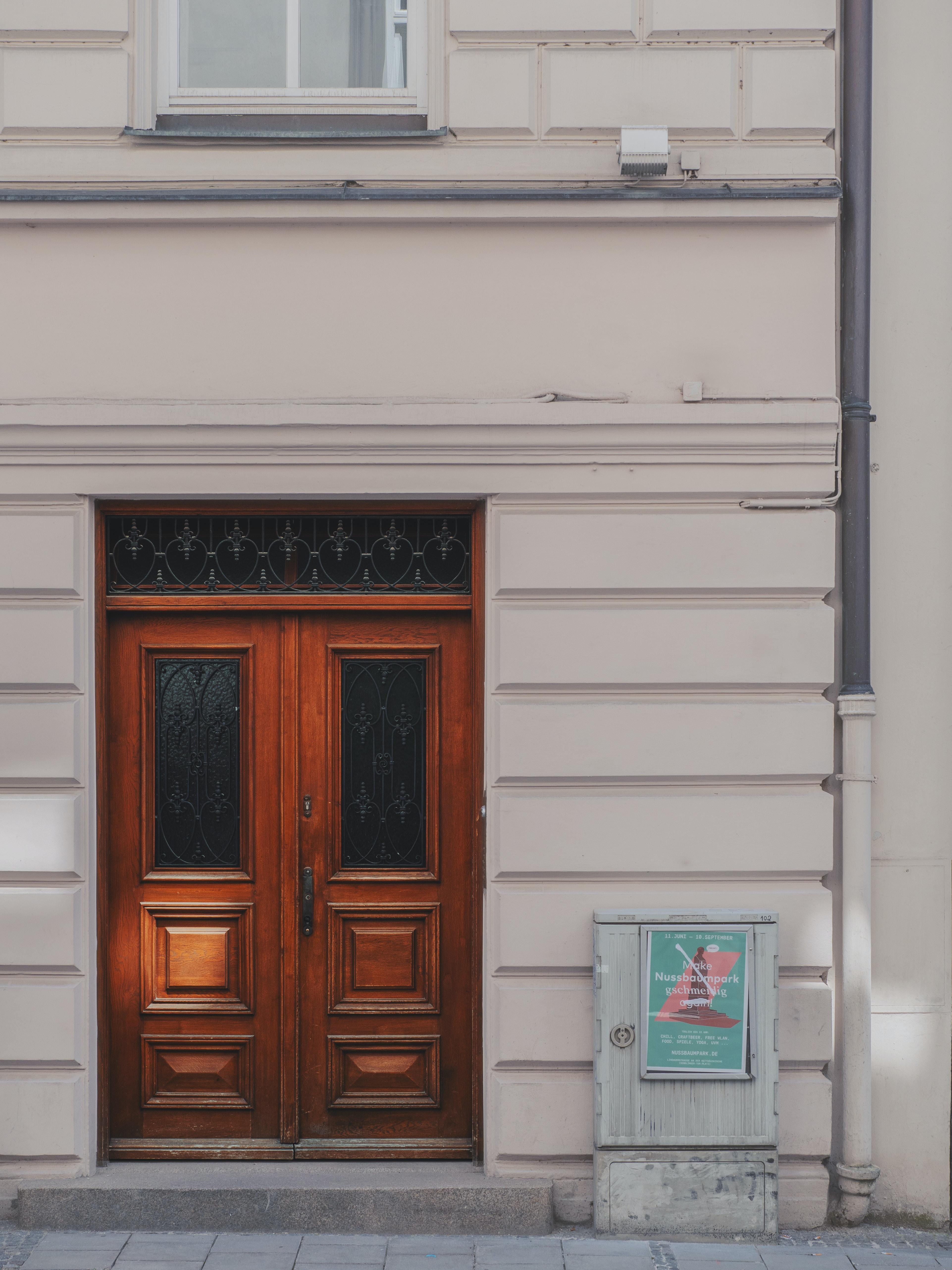 brown wooden door in white building at daytime