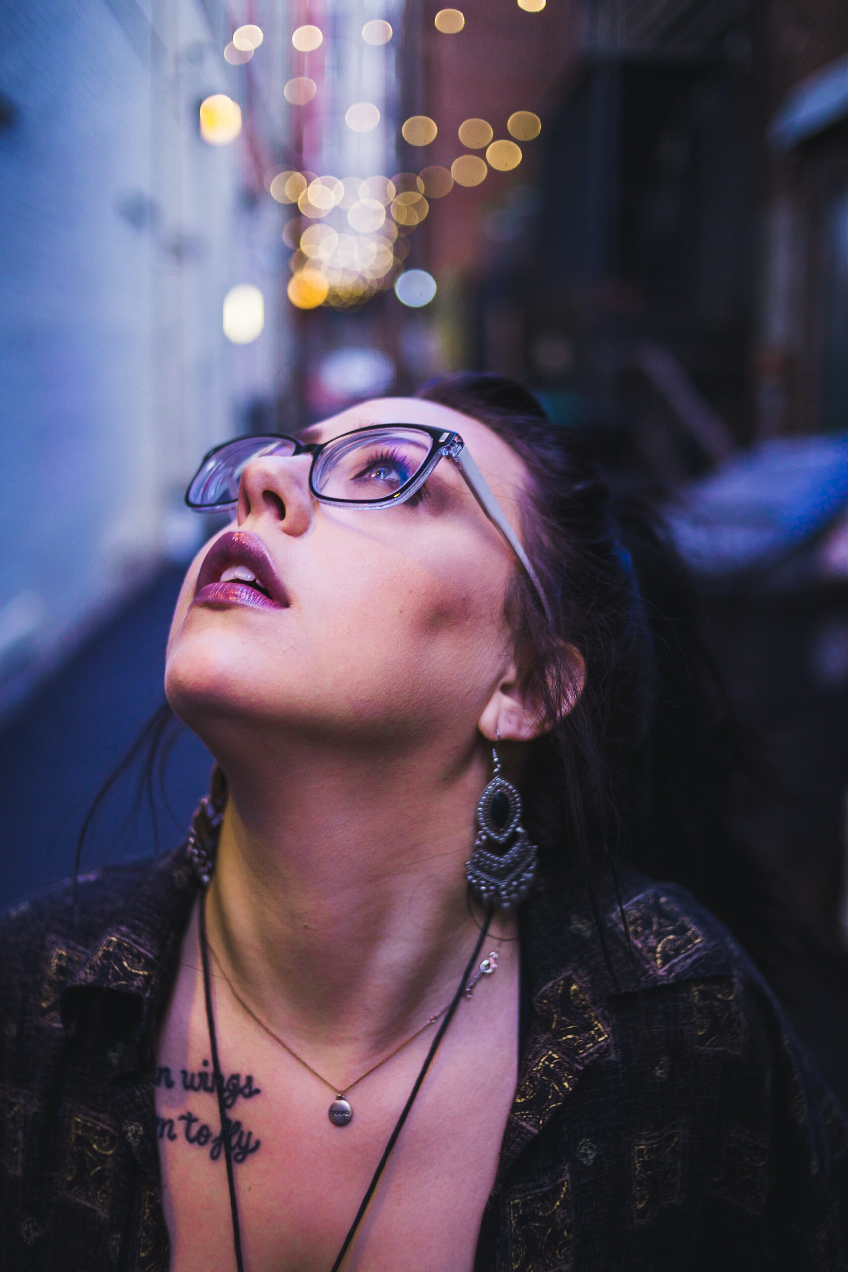 woman looking upwards wearing glasses in selective focus photography
