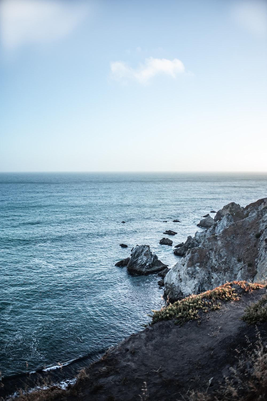 body of water beside rocks