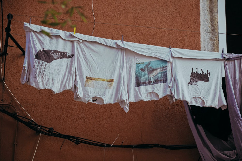 several white shirts hand on clothes wire