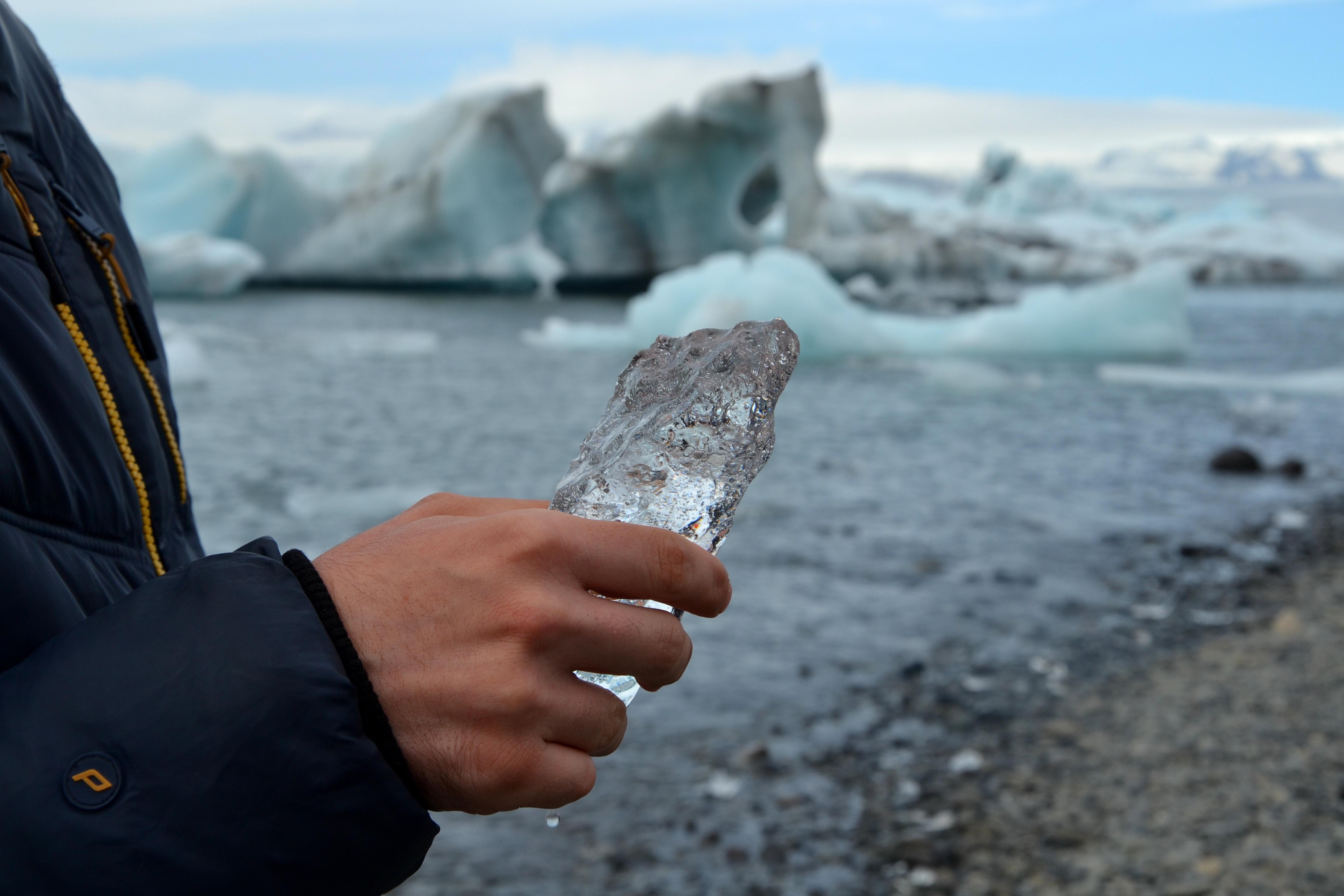 person holding gray stone near the iceberg