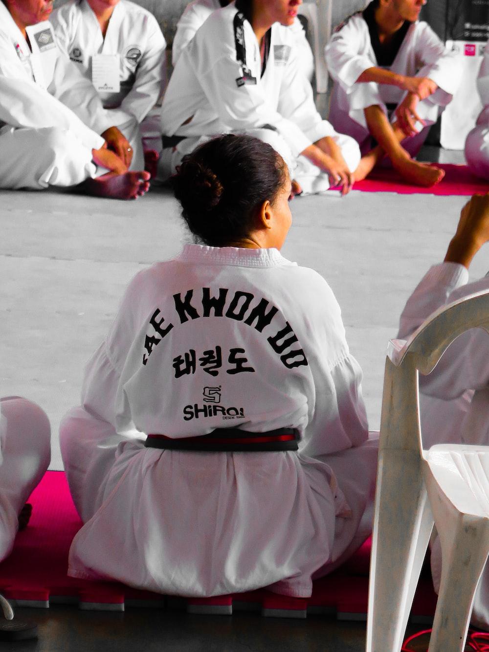 girl wearing karate gi sitting on pink puzzle mat