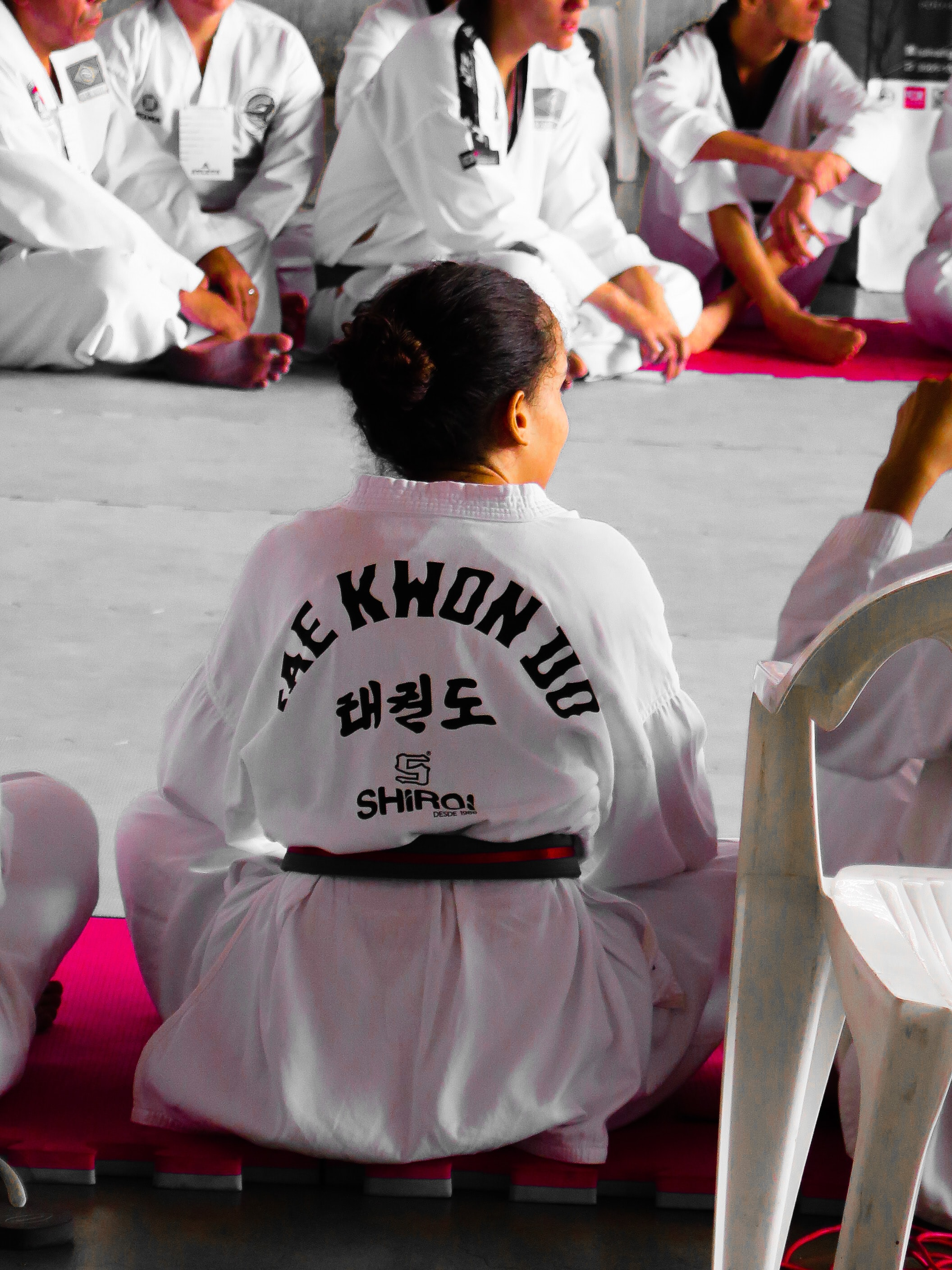 girl wearing karate gi sitting on pink puzzle mat