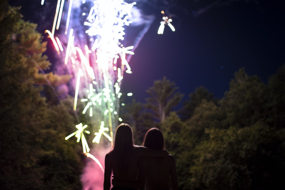 two people standing near firework show