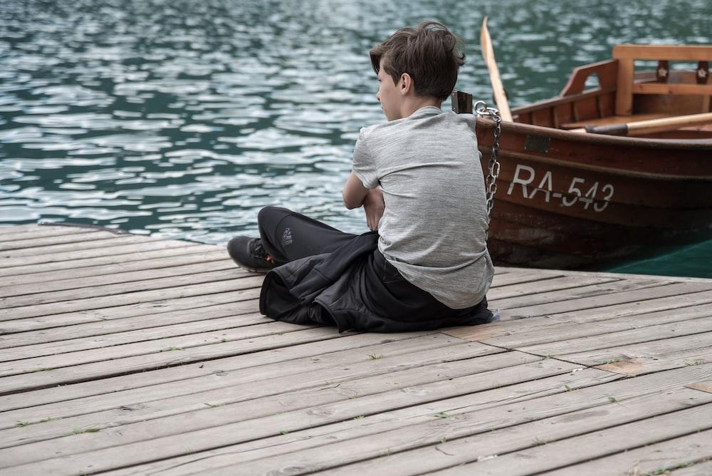 boy sitting on dock