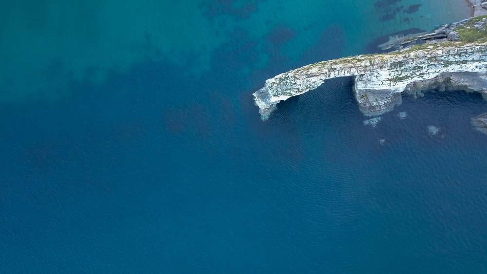 rock formation on water in aerial view
