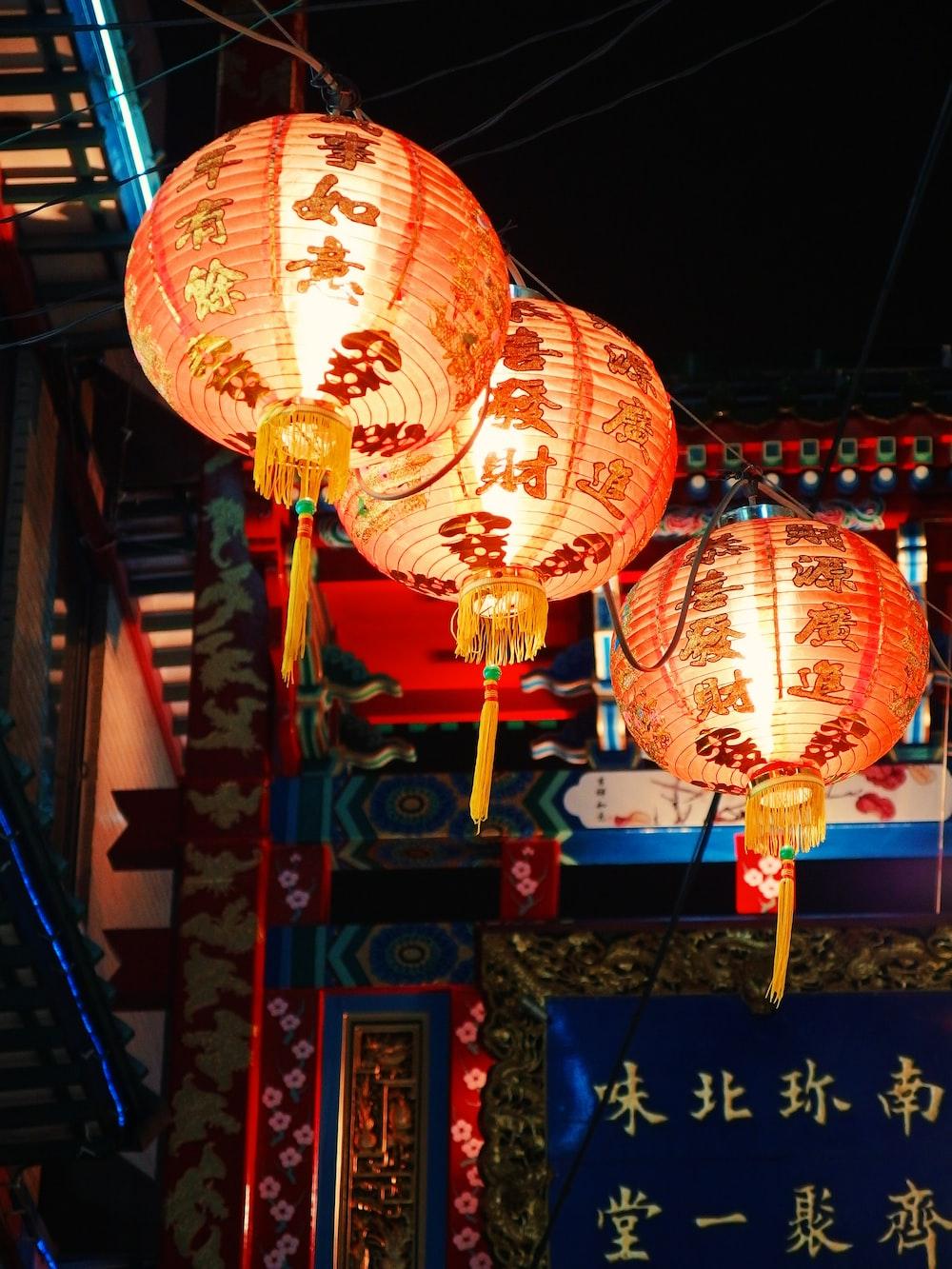 three orange hanging lanterns