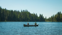 two persons on canoe during daytime
