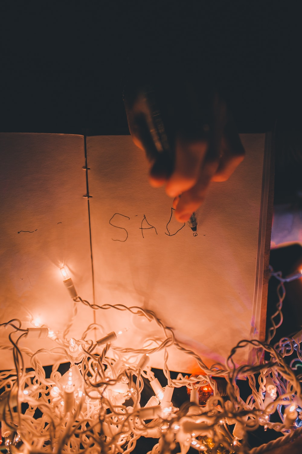 person writing on book with lighted string lights