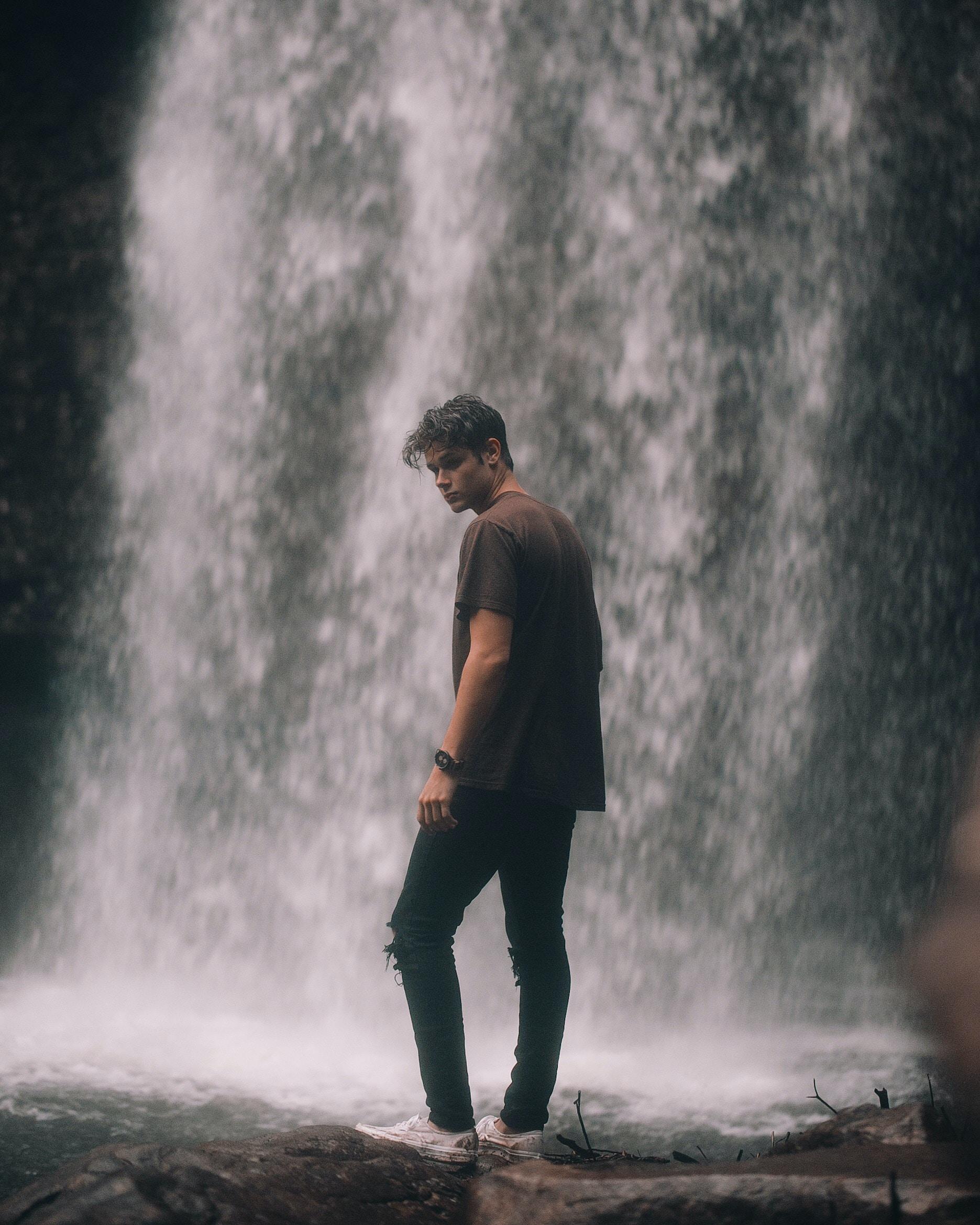 man standing near waterfall