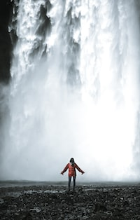 woman standing near waterfalls during daytime