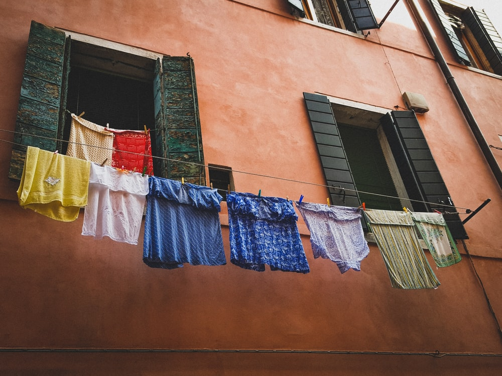 assorted clothes hanged near building