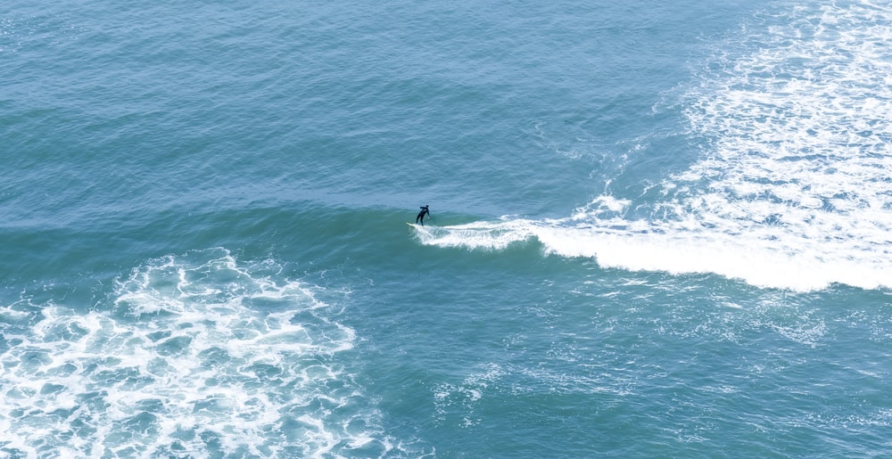 man surfing on body of water during daytime