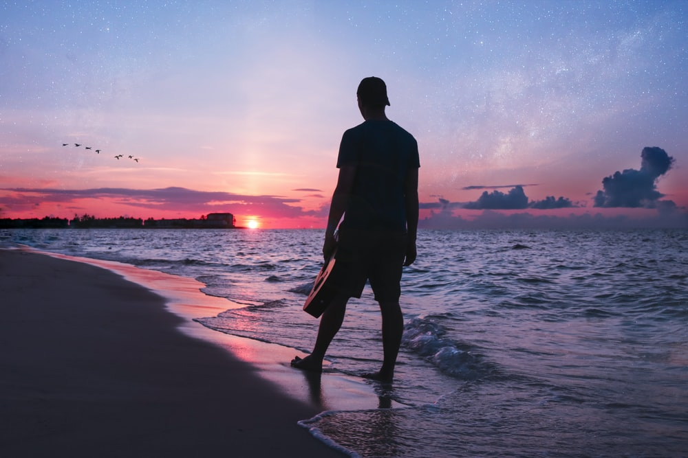 man holding guitar walking on shoreline
