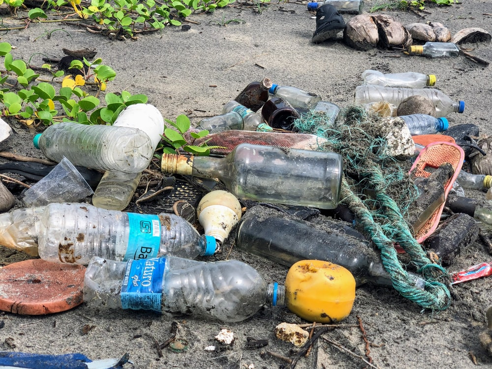assorted garbage bottles on sandy surface