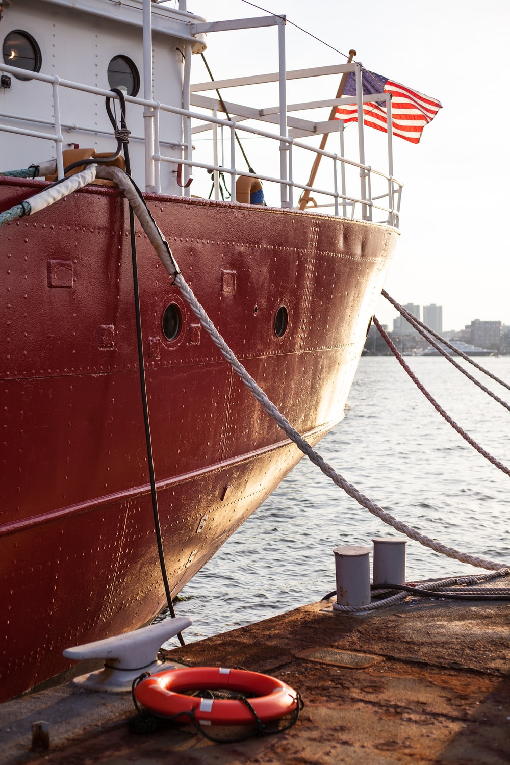 red and white ship docking on dockside at daytime