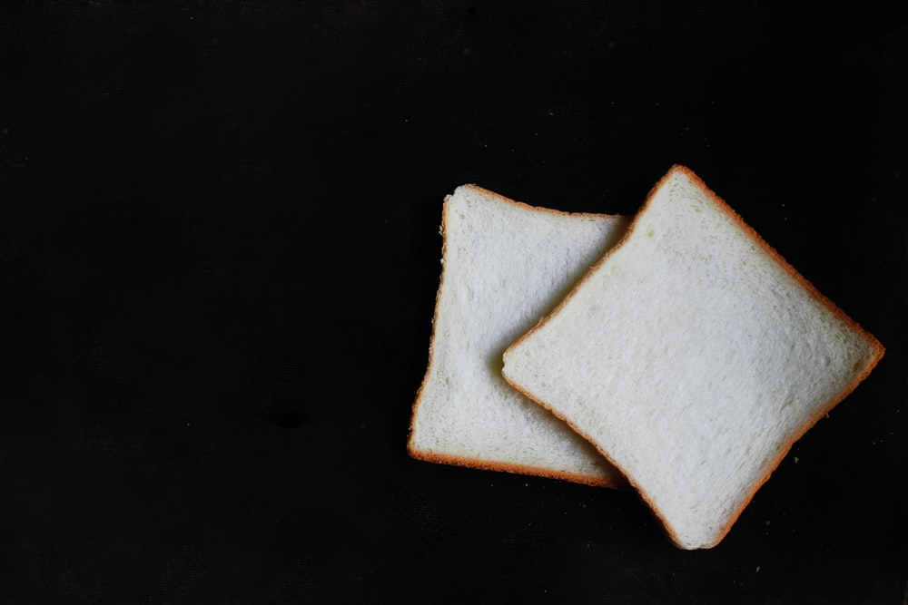 two slices of breads on top of black surface