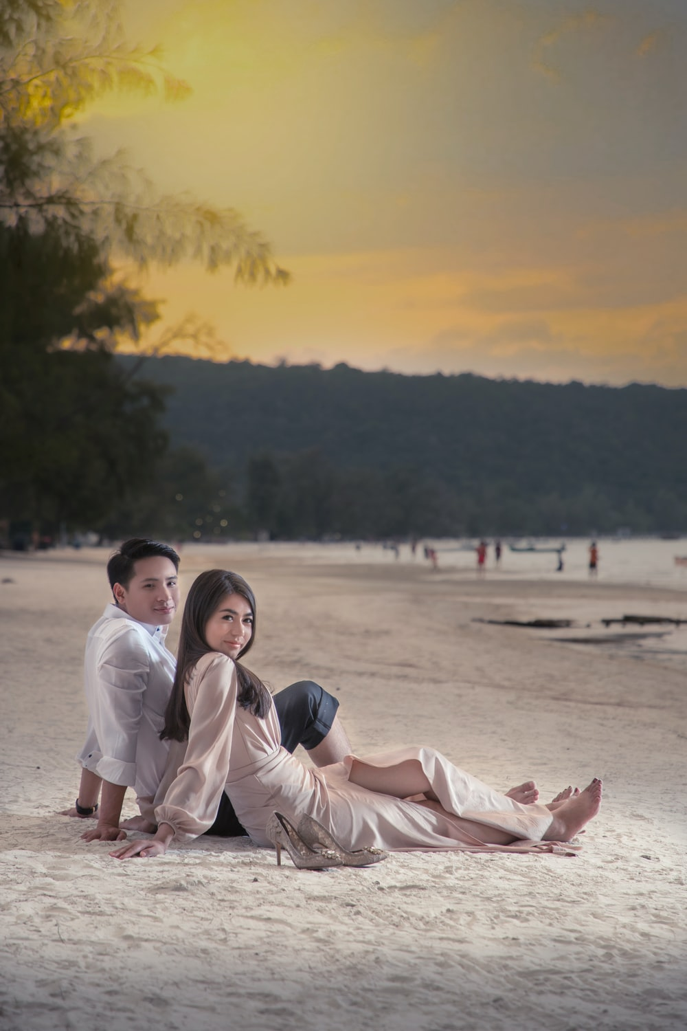 man and woman sitting on sand during sunset