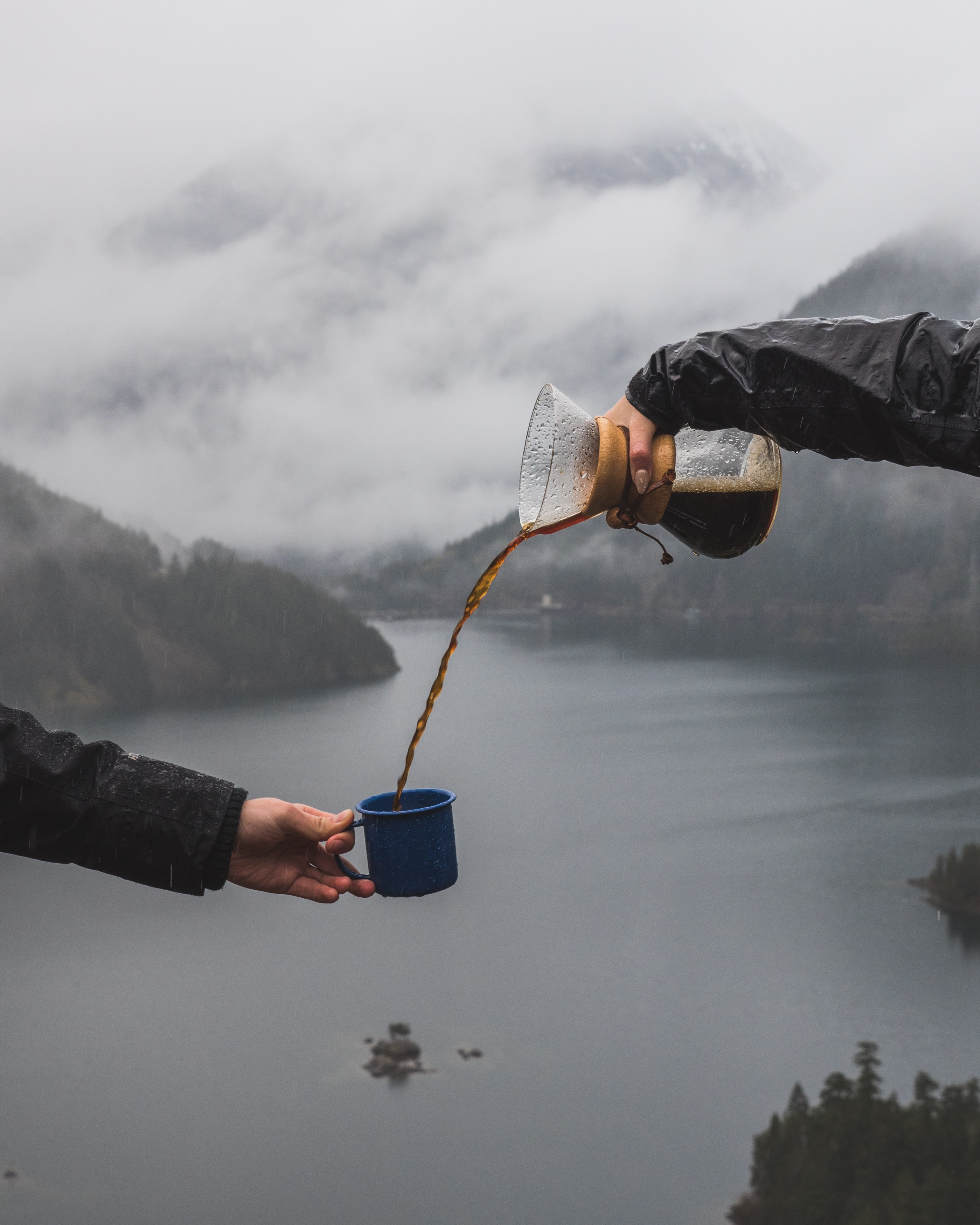 person pouring coffee to the another person's cup near body of water