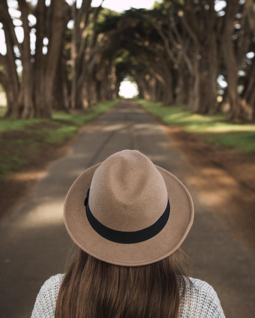 woman walking on road between trees during daytime