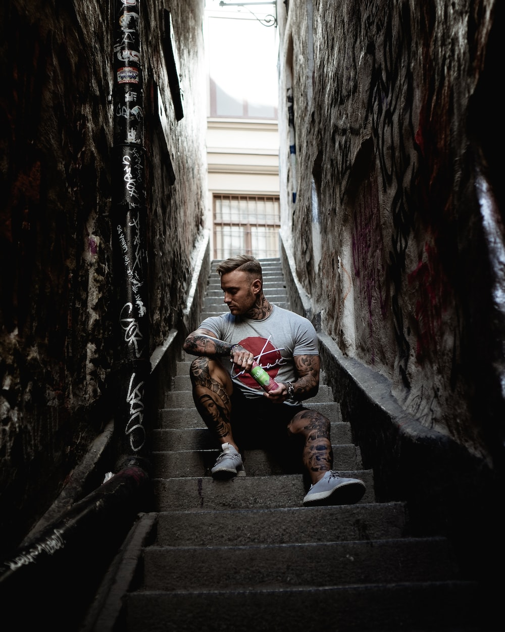 man sitting on stair in narrow pathway