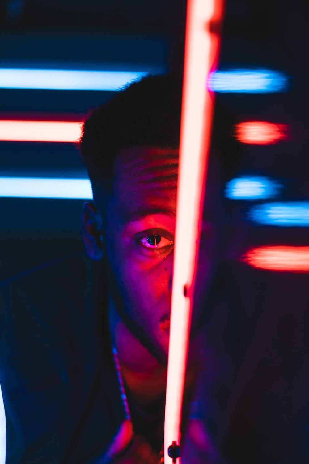 man peeping on red LED lamp