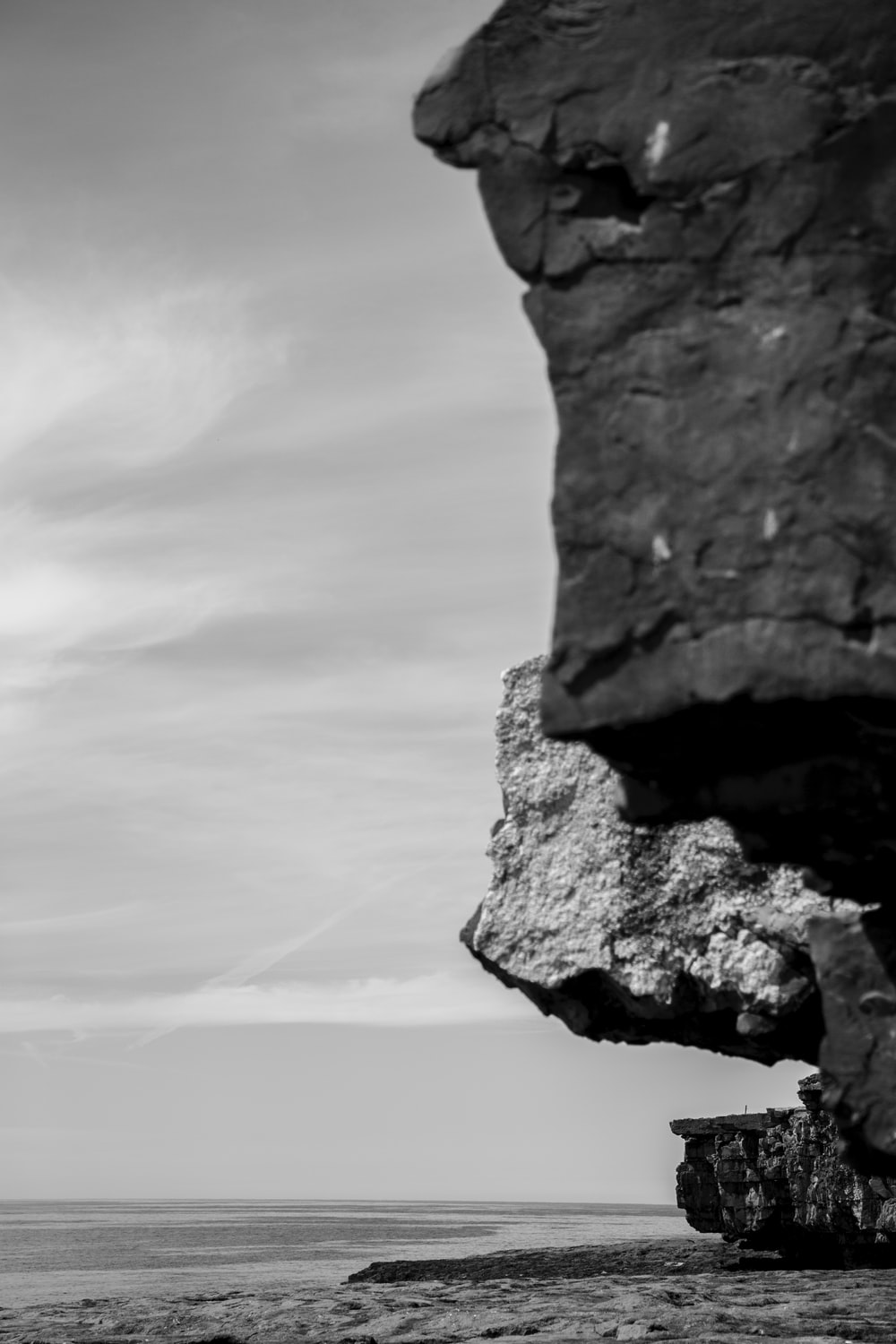grayscale photography of cliff viewing body of water