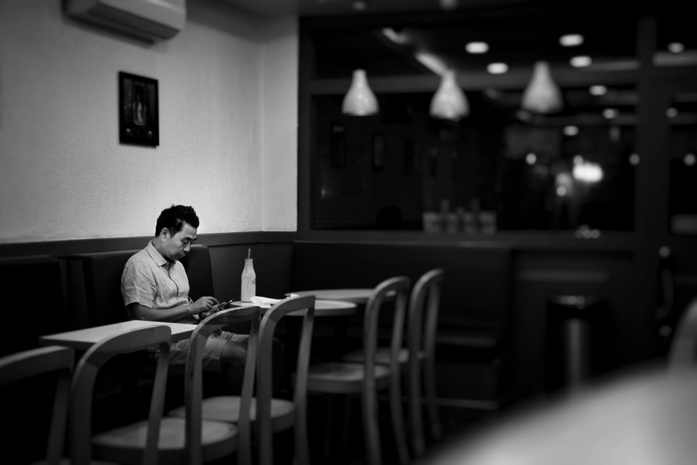 man sitting on cafe while holding smartphone