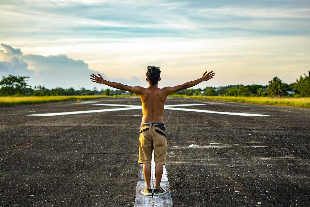 man raising hands standing on concrete road