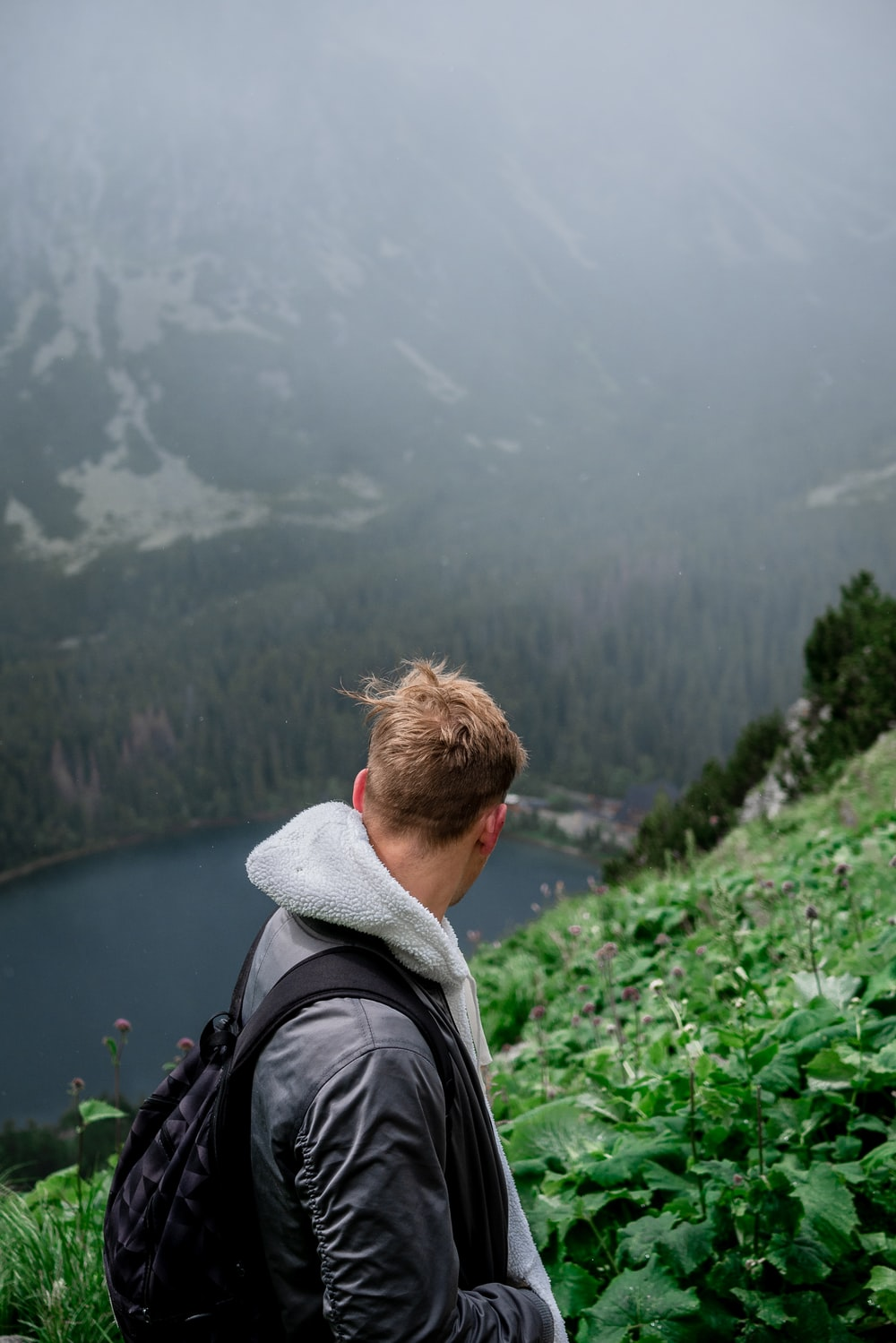 man standing on mountain overlooking lake during daytime