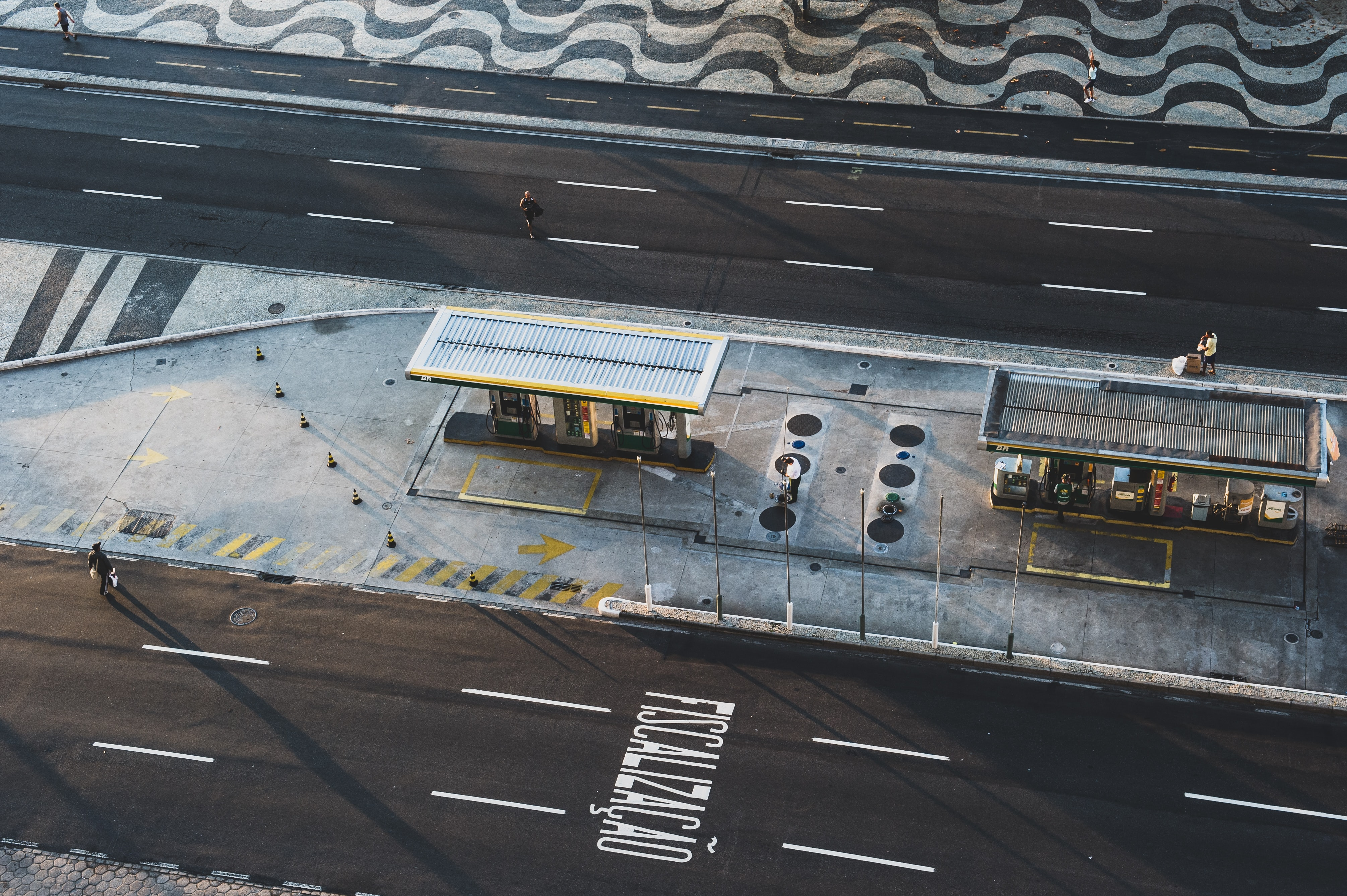 aerial photo of man walking across road approaching store