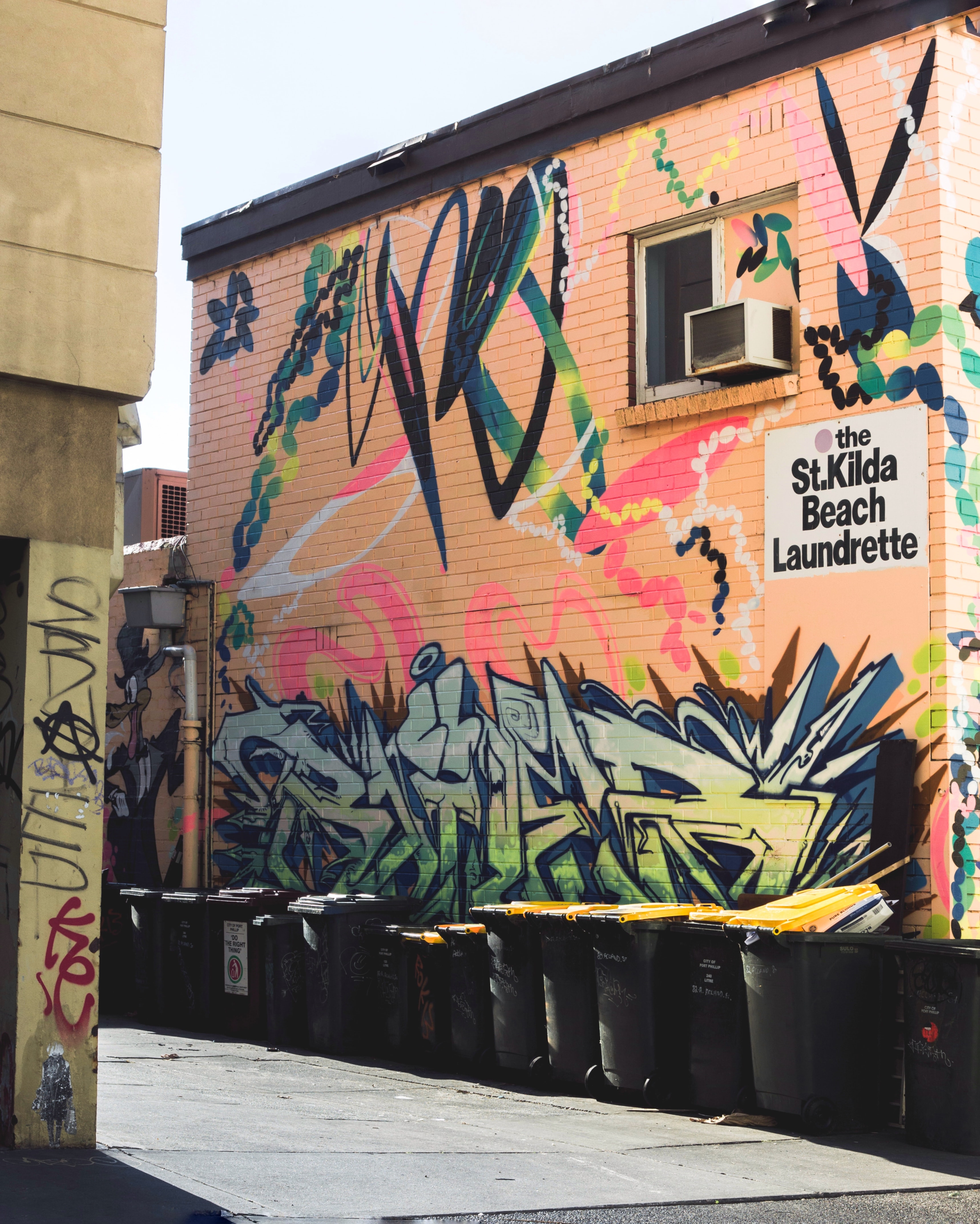 green and orange grafitti wall art beside gray alley