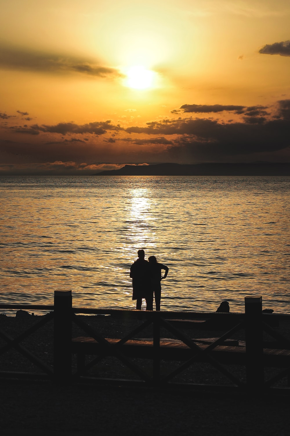silhouette of couple standing near sea