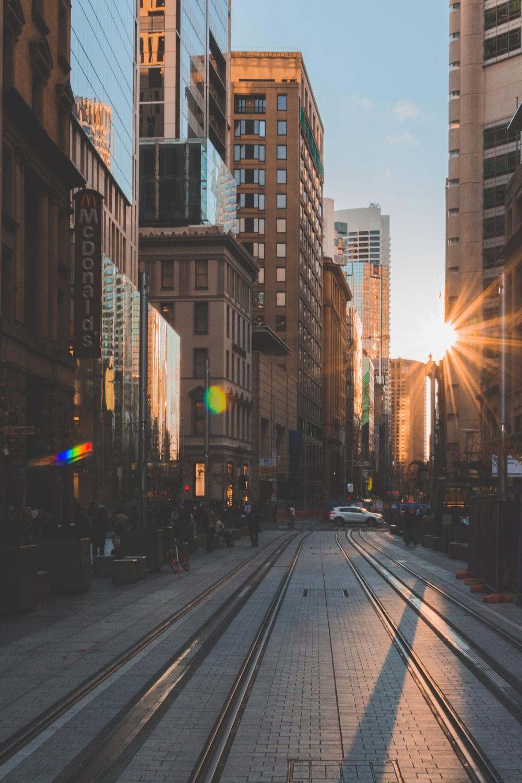 people walking on roadside between buildings with sunlight