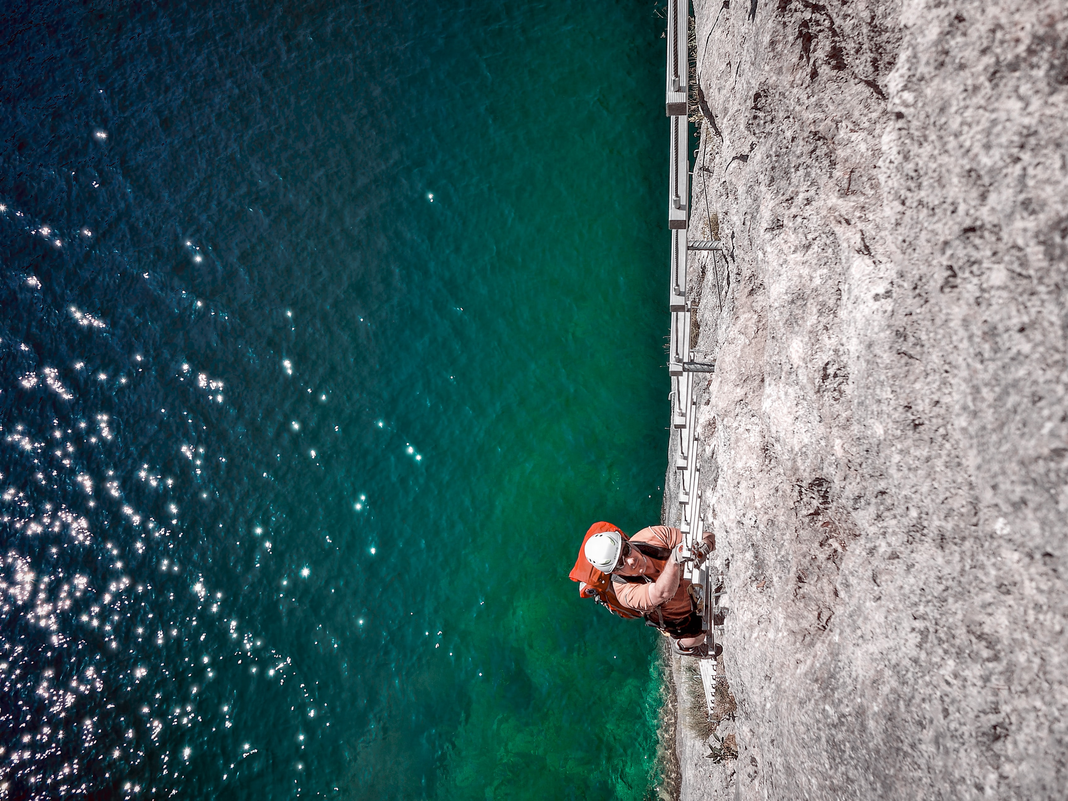 man climbing on ladder above sea level