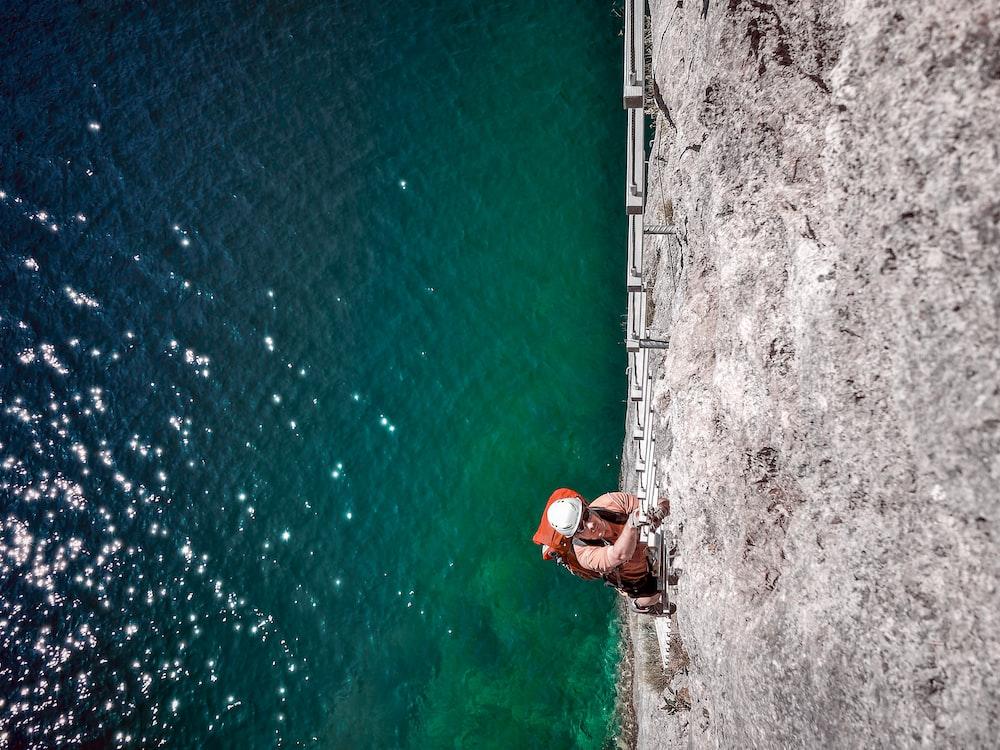 man climbing on ladder above sea level