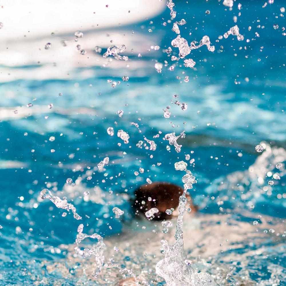 person diving on pool splashing water