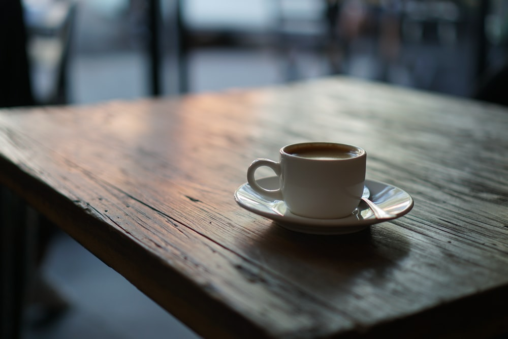 white ceramic cup on saucer on top of wooden table