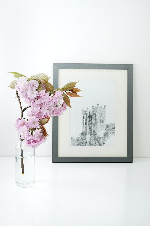 rectangular gray wooden photo frame beside pink flower